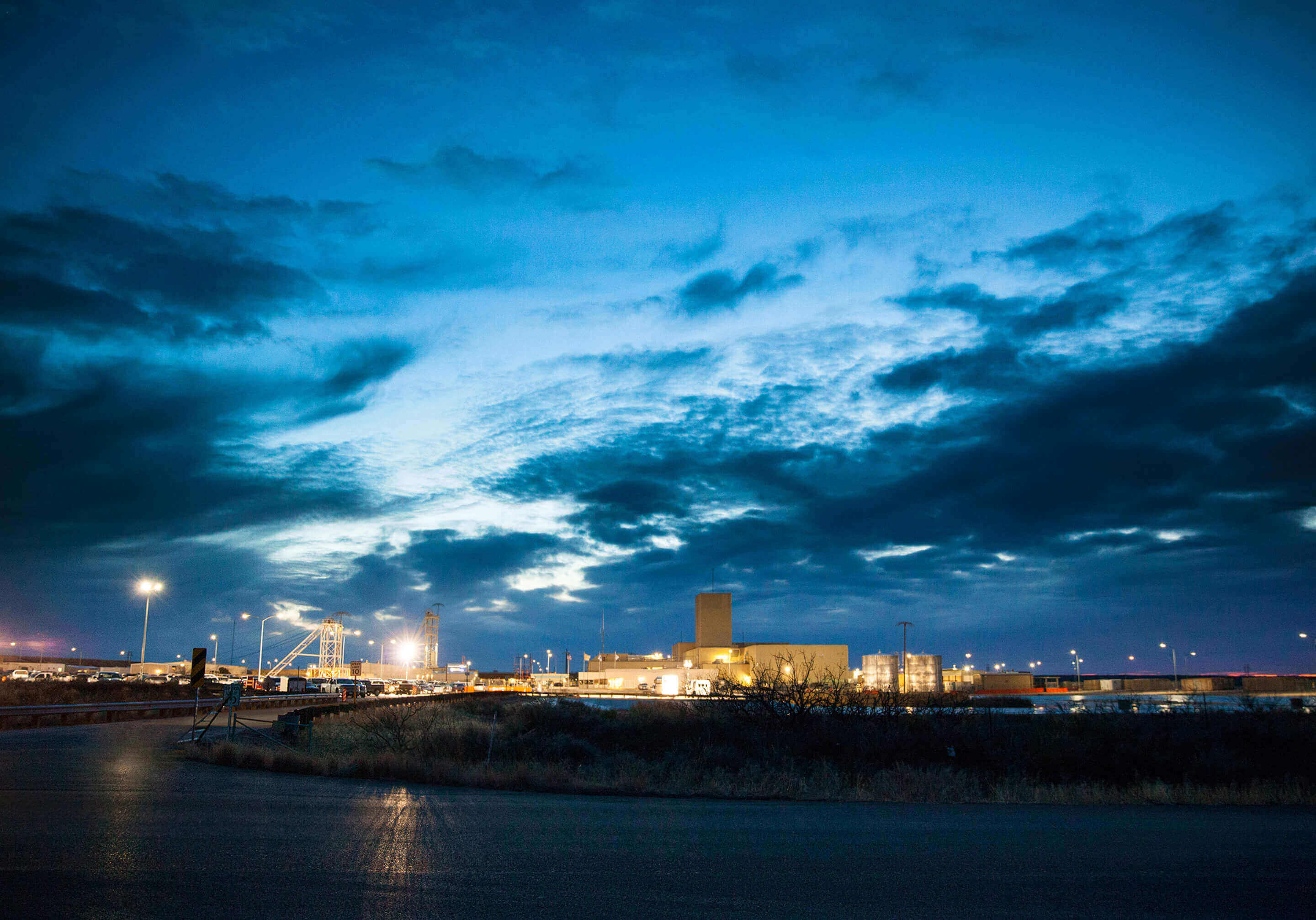 Landscape image of the Waste Isolation Pilot Plant at dusk with with dark blue clouds overhead